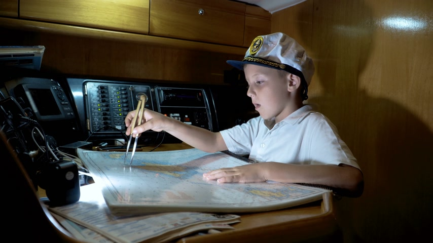 rehberlik : Child captain of the yacht paves the route on the map Stok Video
