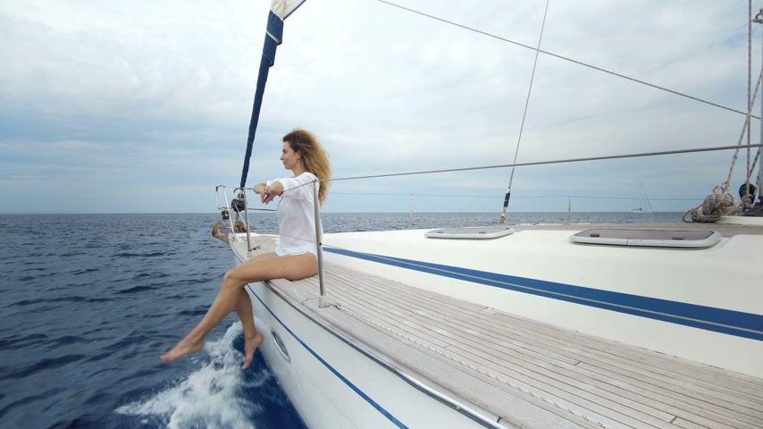 opalenizna : Beautiful girl in the swimsuit sits on the bow of the yacht and sunbaths in the sea
