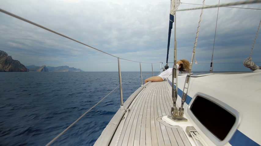 denizciler : Girl sitting on the bow of sailing boat on sea. Stok Video