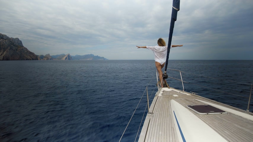 парусное судно : Girl standing on the bow of sailing boat on Mediterranean sea.