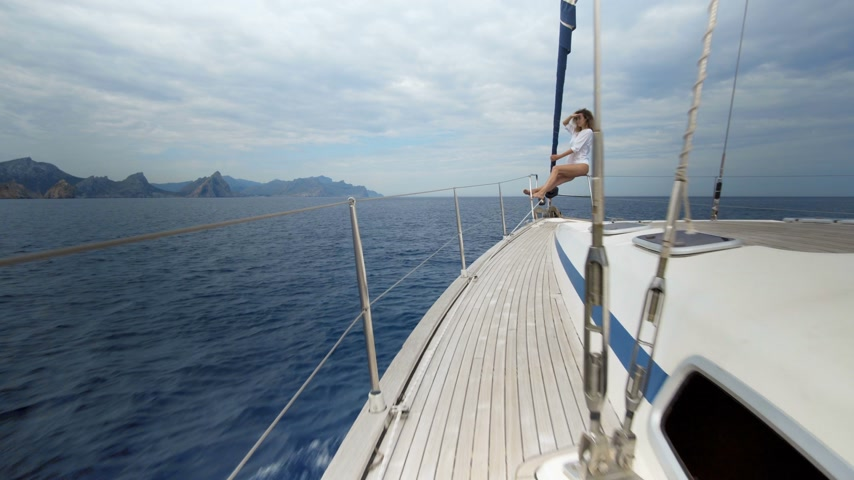 bronzlaşma : A beautiful girl looks into the distance. The wind blows her hair, poses and tans on a yacht. Blue ocean. Stok Video