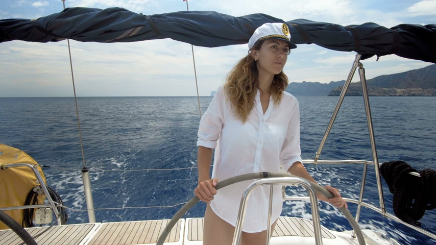 yatçılık : Young woman at the helm of a yacht in the open sea Stok Video
