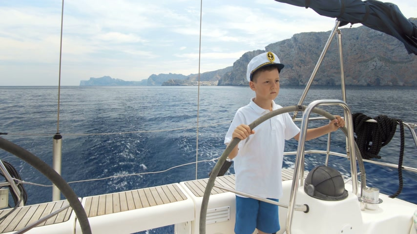 command : Litle children captain at the helm controls of a sailing yacht during race. Stock Footage