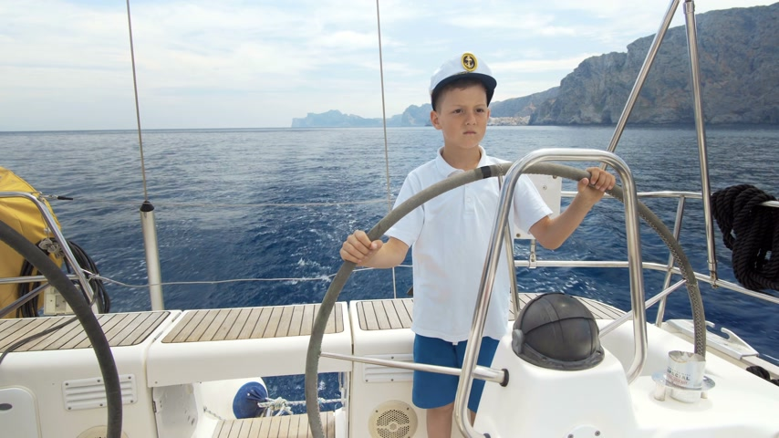 командир : Litle children captain at the helm controls of a sailing yacht during race. Стоковые видеозаписи