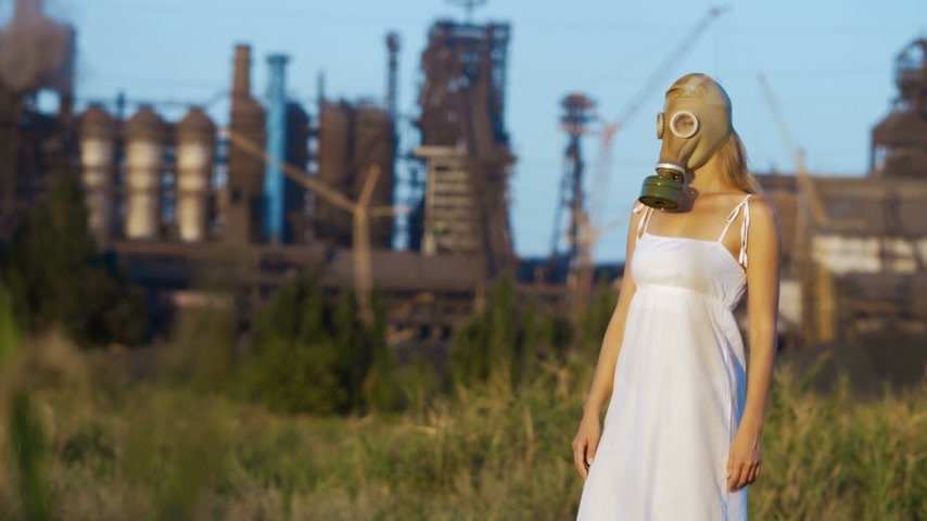 hazmat : Woman in a gas mask on a background of smoky pipes of a factory Stock Footage