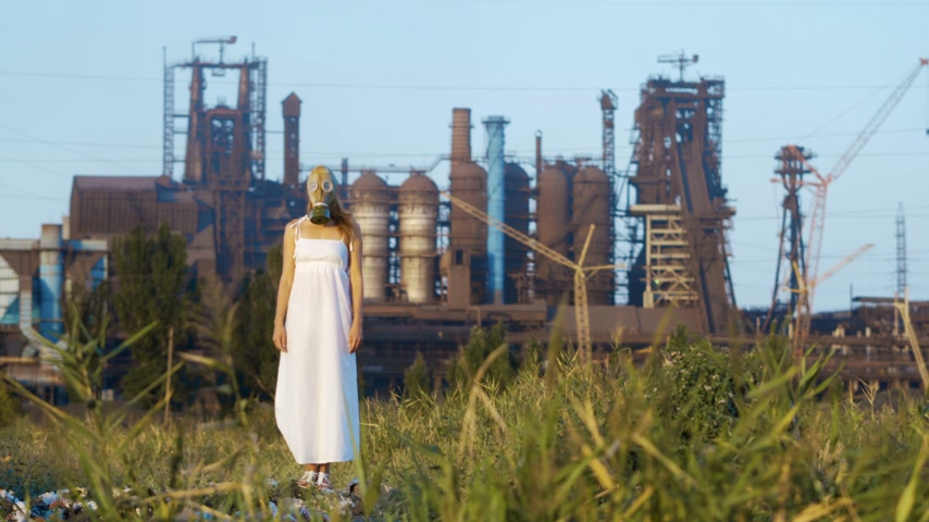 protective suit : Woman in a gas mask on a background of smoky pipes of a factory Stock Footage