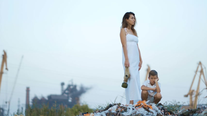 defin : Mom and son. Garbage dump. Industrial factory on a background. Enviroment pollution concept.
