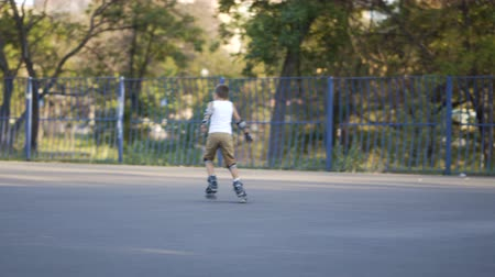 inline : Rides roller skates. Boy rolls on rollers Stock Footage
