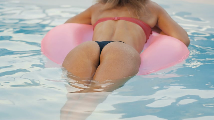 volleyball : Girl in the pool swims on an inflatable donut of pink color Stock Footage