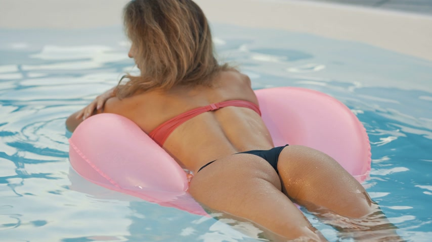 feliz : Girl is swimming in the pool on a pink rubber ring. Beautiful Ass