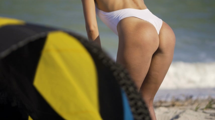 zadek : Rear view beautiful young girl beach sand off ass slow motion pumping a kite tropical vacation close up shot