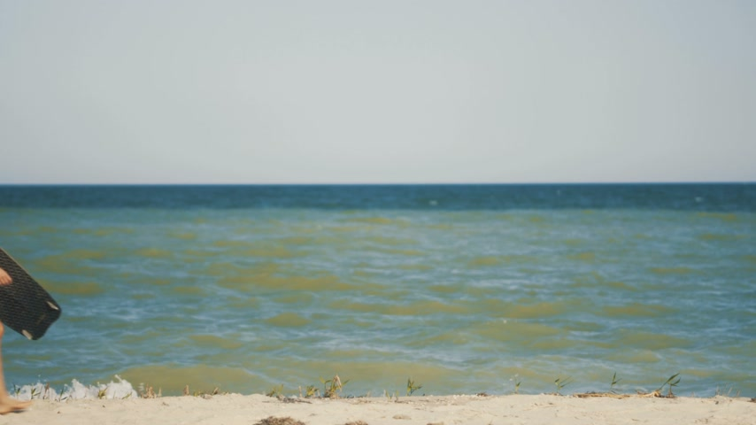 kite boarding : Girl with kiteboard is walking along the beach tropical beach at sunset . Girl holding board in hand Stock Footage