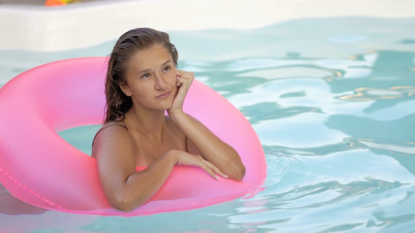 ananas : Happy girl relaxing on inflatable pink doughnut float. Young woman in bikini enjoying summer vacation drinking cocktails on pink floatie in pool