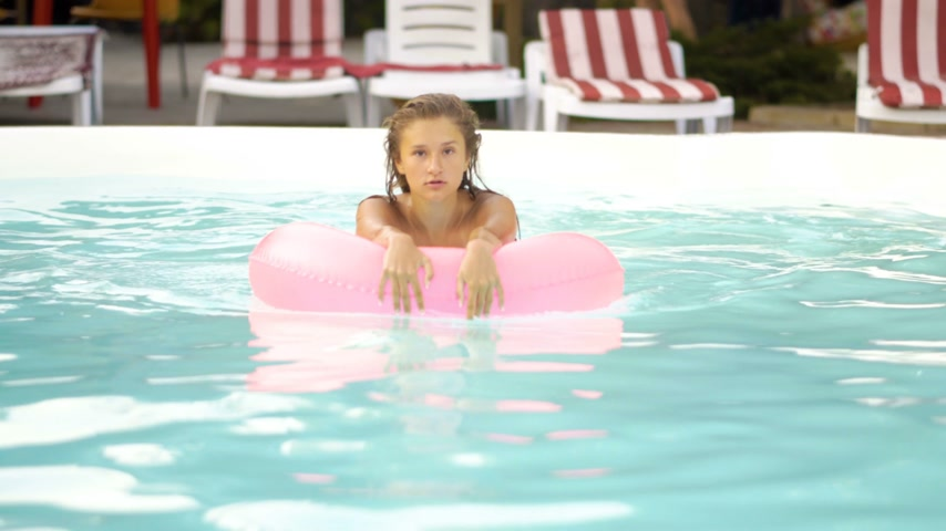 dişlek : Happy girl relaxing on inflatable pink doughnut float. Young woman in bikini enjoying summer vacation drinking cocktails on pink floatie in pool