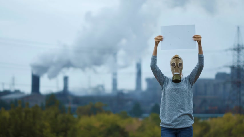 defensiva : Woman in a gas mask on a background of smoky pipes of a factory Stock Footage