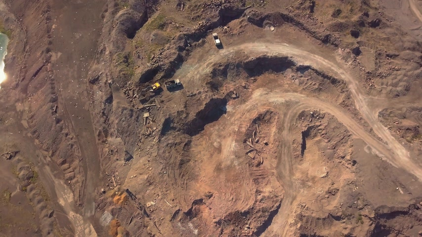 kövület : Aerial view of working excavator in the opencast mine. Camera flight over industrial landscape. Stock mozgókép
