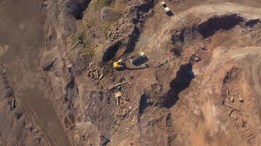 taş ocağı : Aerial view of working excavator in the opencast mine. Camera flight over industrial landscape. Stok Video