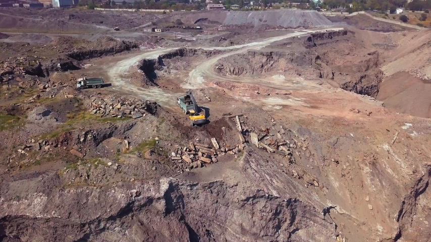 bagger : Aerial view of working excavator in the opencast mine. Camera flight over industrial landscape. Stock Footage