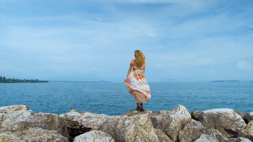 wanderlust : girl in a beautiful dress is standing on the coast Stock Footage