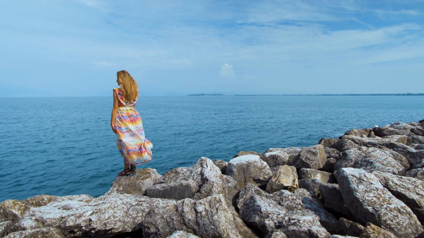 amalfi : girl in a beautiful dress on stones looking at the ocean Stock Footage