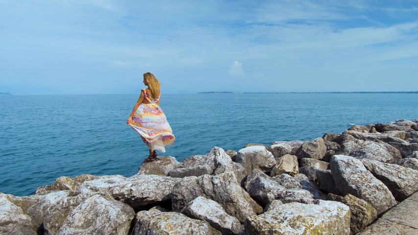 keşif : girl in a beautiful dress on stones looking at the ocean Stok Video