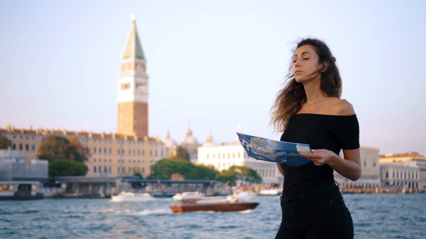cesaret : Attractive young woman traveling in Europe and exploring beautiful sightseeing in Barcelona, sunshine lens flare, slow motion, hipster girl wearing glasses and holding tourist map, enjoying holiday Stok Video