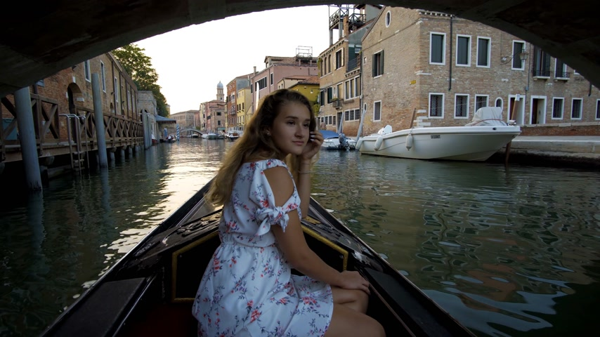 égua : Beautiful girl in dress riding on gondola, Venice, Italy.