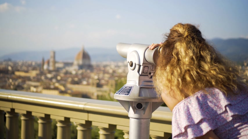 binocular : young girl looks at the landscape with the spyglass. Florence, italy