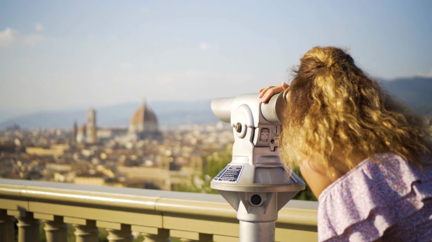 lookout point : young girl looks at the landscape with the spyglass. Florence, italy
