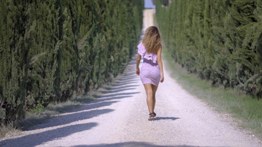 yay : Back view a woman in a dress goes away into the distance along the cypress alley, of decorative and neat tall green trees in the park. On a Sunny summer day. 4k Stok Video