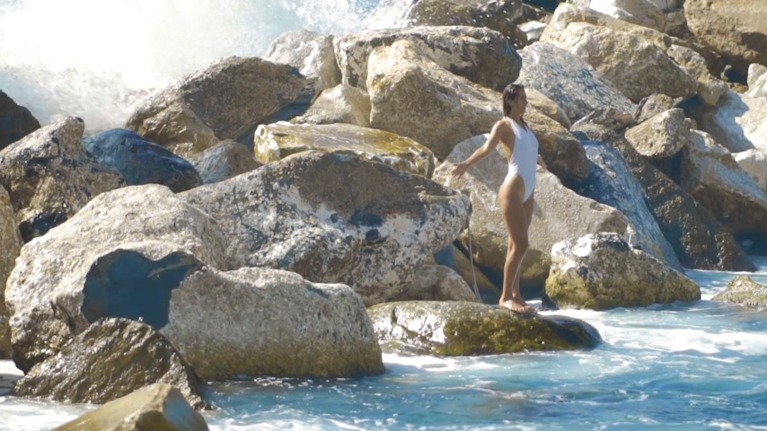 spraying : the waves break on the stones and sprinkles a girl in a bathing suit standing on the rocks, slow motion
