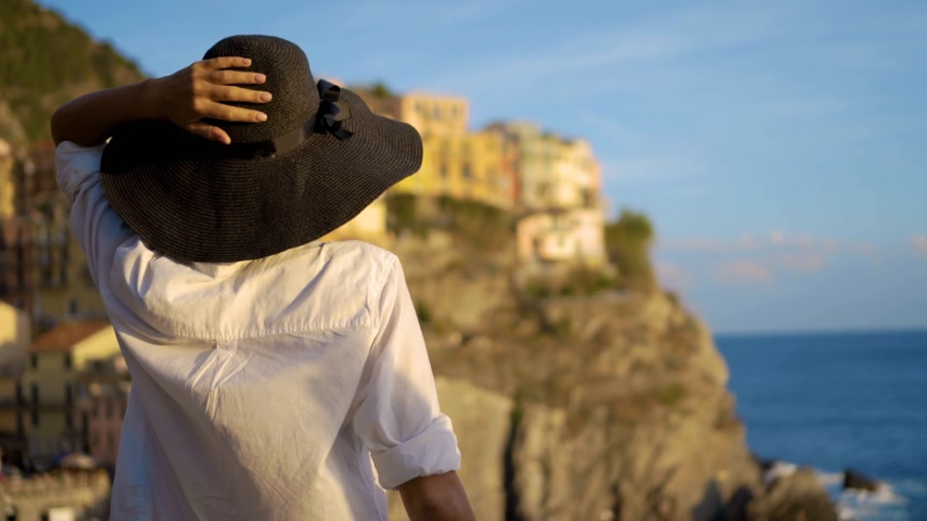liguria : girl in a hat looks at the city of Manarola Italy Stock Footage
