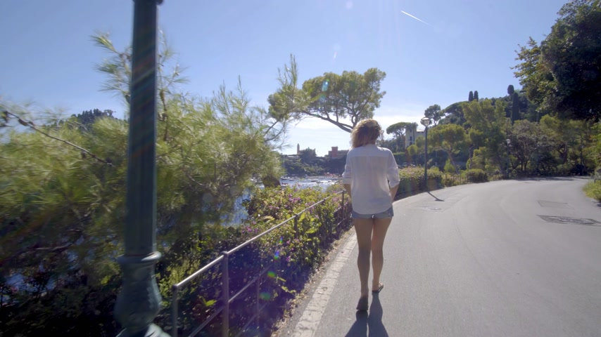 égua : girl walking and looking down on the bay portofino italy Stock Footage
