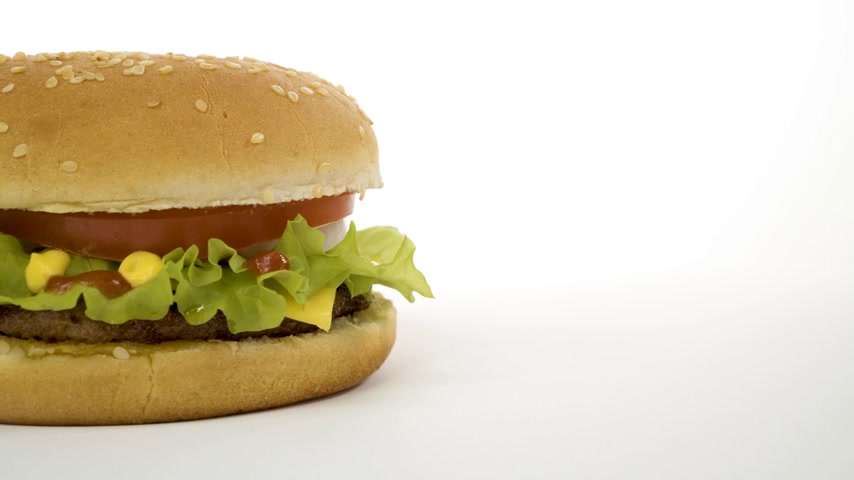american cuisine : Rotation of an appetizing burger on a white background.