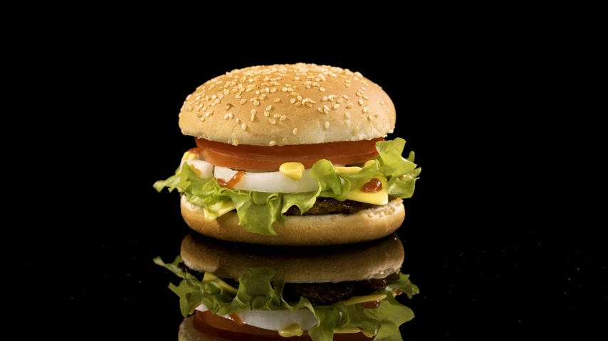 bacon burger : Rotation of delicious burger over black background.