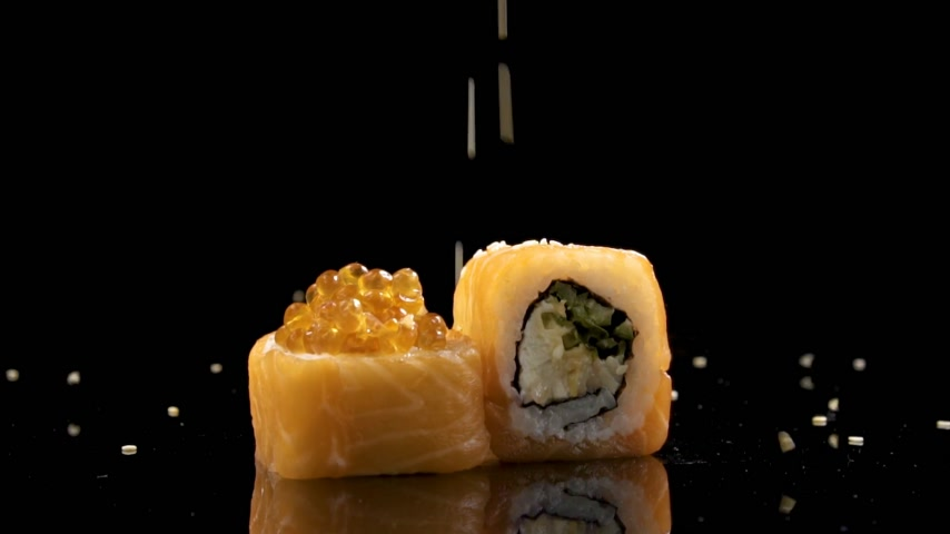 kaviár : Slowmo sushi roll with salmon and caviar on black background rotating.
