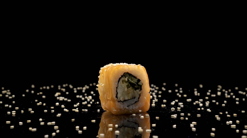 kaviár : sushi roll with salmon and caviar on black background rotating.