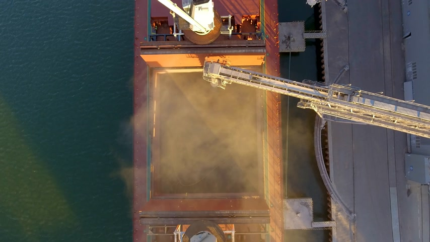 freighter : Aerial view of big grain elevators on the sea. Loading of grain on a ship. Port. Cargo ship