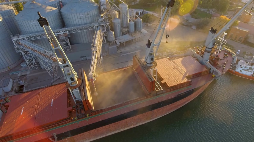 unload : Aerial view of big grain elevators on the sea. Loading of grain on a ship. Port. Cargo ship