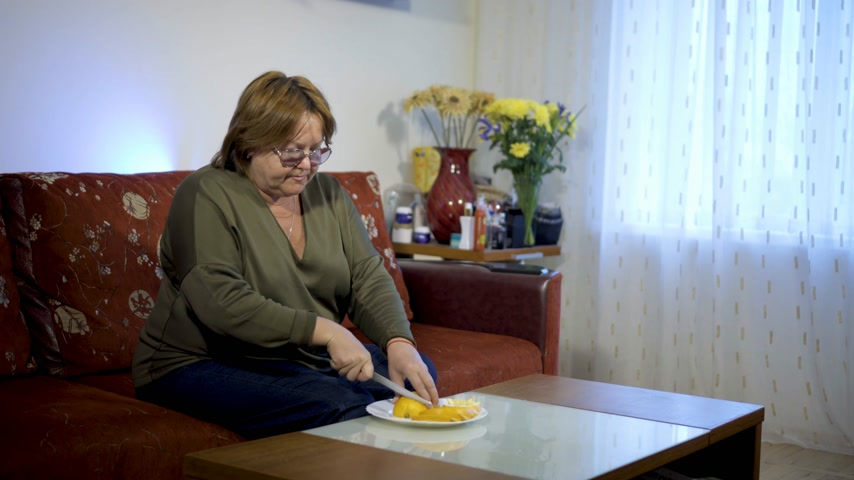 tombul : Woman age eats fruit at home on the couch. Concept of healthy food Stok Video