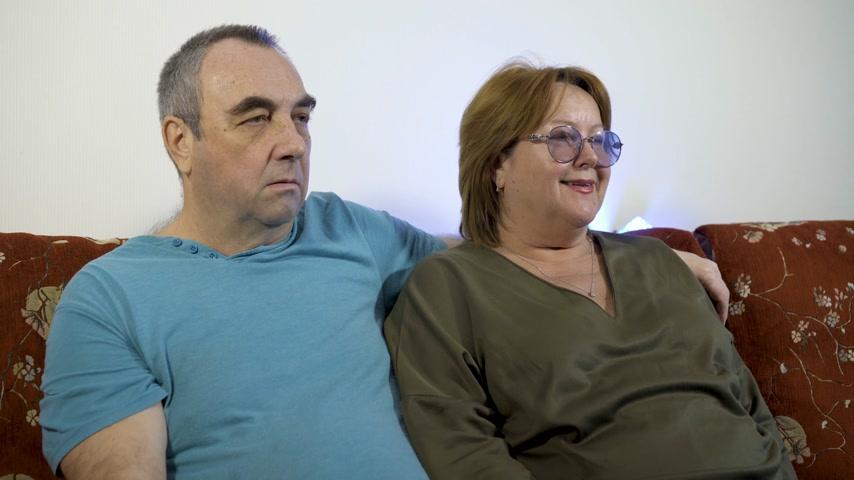 switching : Portrait of a happy mature couple in their home watching tv together