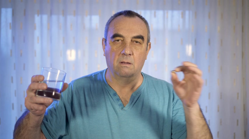 dose de : Aged person with pill. Elderly man holding pill and glass of water. Health problem concept.