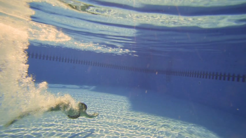 yüzer : the Woman in Bikini swimming underwater with beautiful sun flares in slow motion. Stok Video