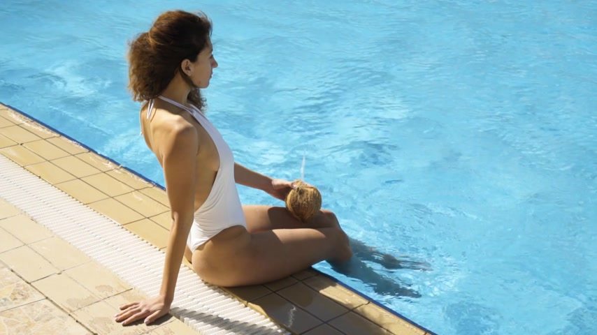 feliz : The girl in a white bathing suit sitting near the pool Vídeos