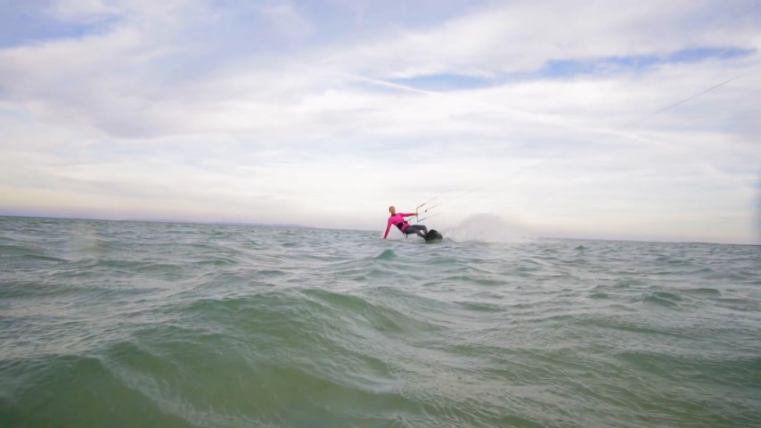 kitesurfer : SLOW MOTION: Female kite-boarder riding and splashing water into camera
