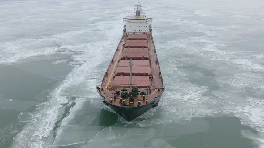 estreito : Cargo ship sailing on frozen sea in extreme winter conditions aerial shot. Sailing in narrow fairway channel made by icebreaker vessel. Water transportation during cold winter season in north. Stock Footage