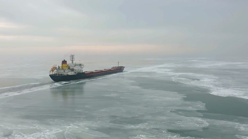 прерыватель : Cargo ship sailing on frozen sea in extreme winter conditions aerial shot. Sailing in narrow fairway channel made by icebreaker vessel. Water transportation during cold winter season in north. Стоковые видеозаписи