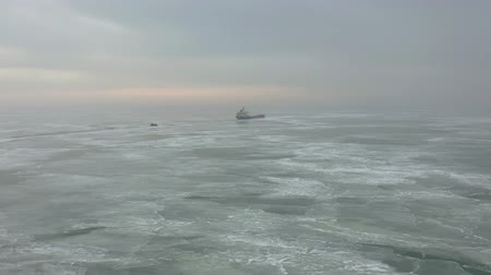 çimenli yol : Cargo ship sailing on frozen sea in extreme winter conditions aerial shot. Sailing in narrow fairway channel made by icebreaker vessel. Water transportation during cold winter season in north. Stok Video