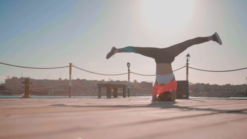 beyin : Girl Does a Headstand at Sunset Near the sea Stok Video