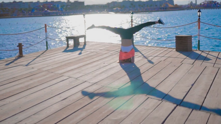 armoni : Girl Does a Headstand at Sunset Near the sea Stok Video